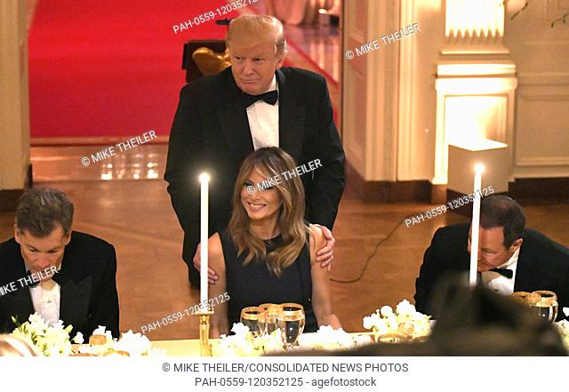 United States President Donald J. Trump shows First Lady Melania Trump to her seat as they attend a White House Historical Association dinner at the White House