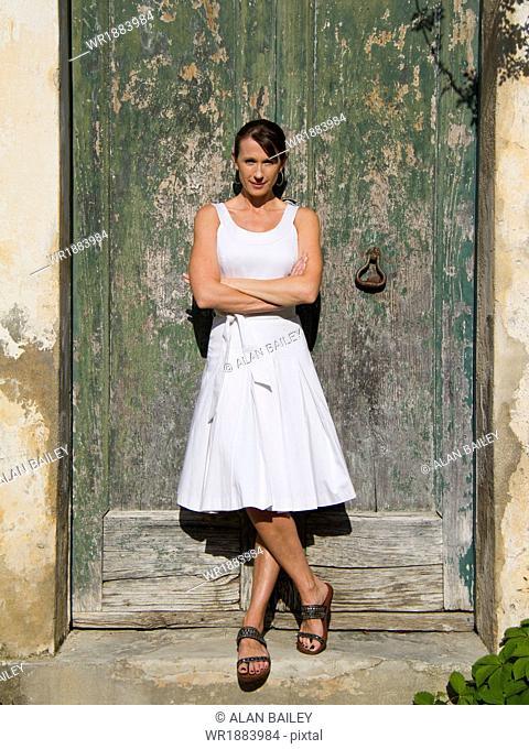 Italy, Ravello, Portrait of woman standing in front of watered wooden door