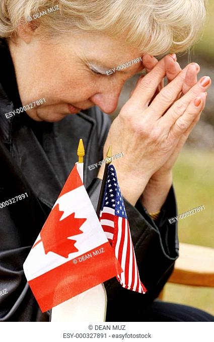 Woman praying over flags from different countries
