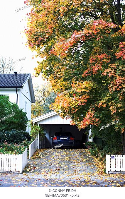 A garage with a parked car by a white house, Sweden