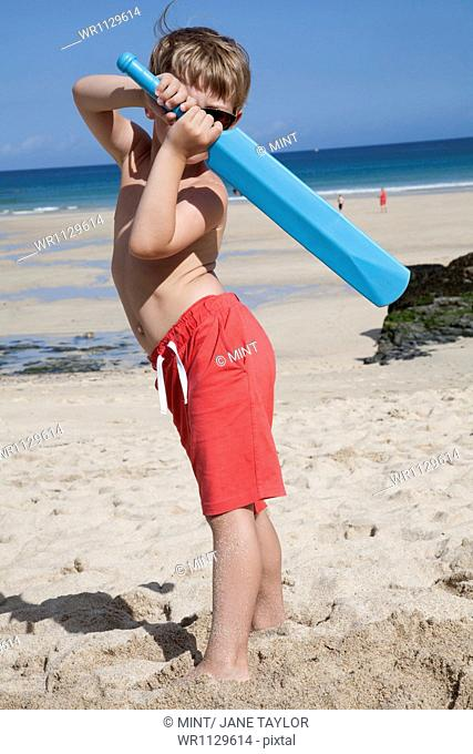 A boy standing on the sand with a small blue cricket bat in his hands