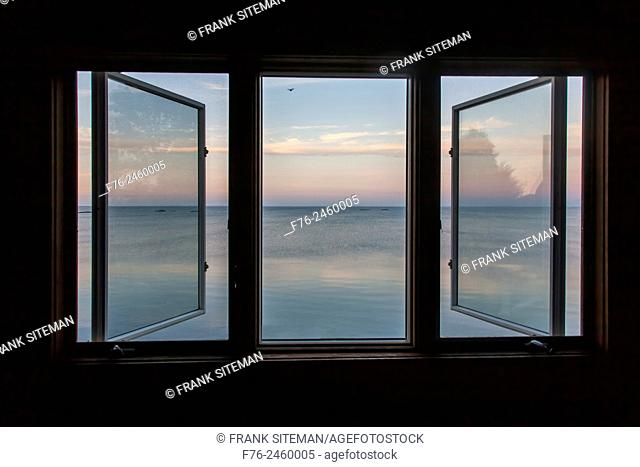 View of the Atlantic Ocean from an upstairs bedroom 3 unit picture window of a large home in Connecticut, overlooking the ocean at dawn, USA