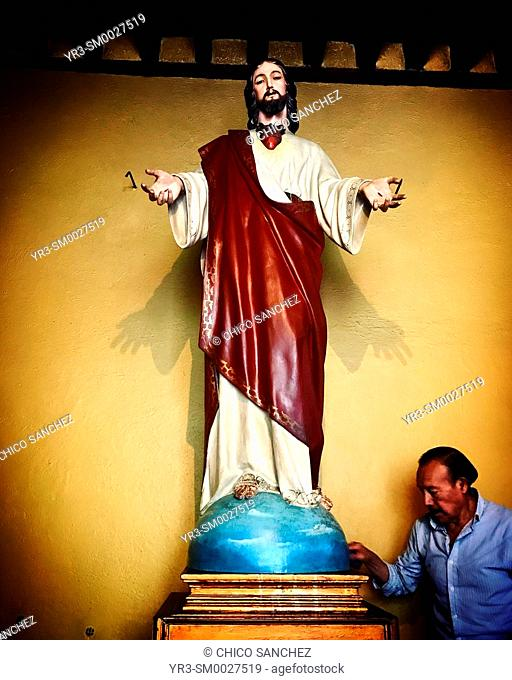 A man cleans a sculpture of the Sacred Heart of Jesus in a church of San Angel, Mexico City, Mexico