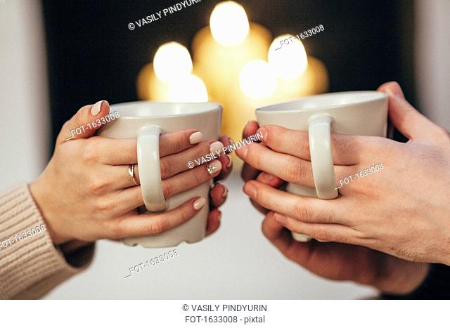 Cropped image of couple holding coffee cups against illuminated candles at home