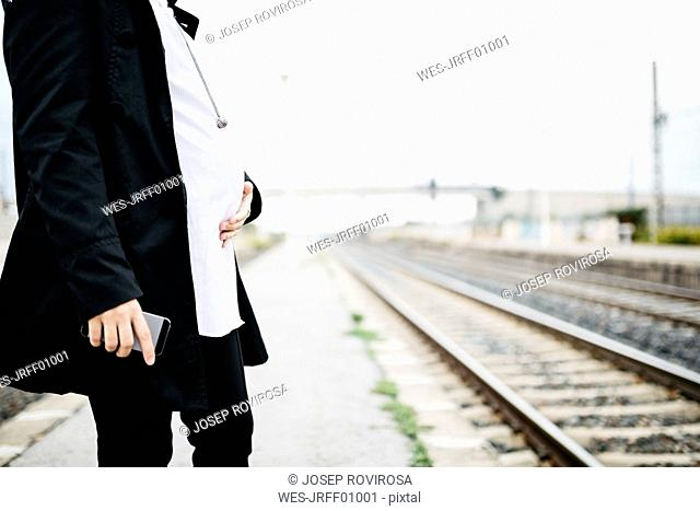 Pregnant woman on platform holding cell phone