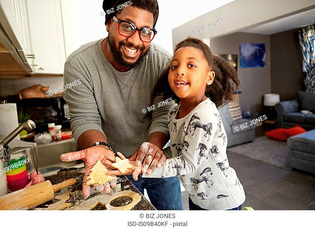 Portrait of father and daughter holding unbaked cookies