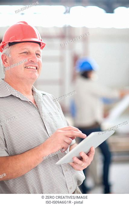 Male construction worker holding a digital tablet