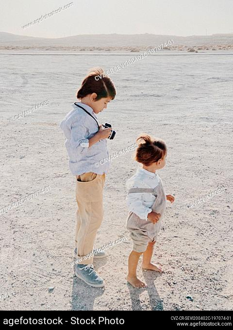 Portrait of a kid holding a camera as another kid stands next him