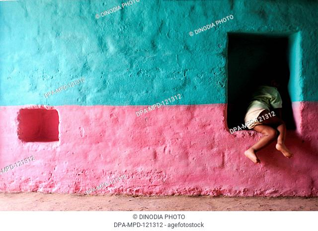 A child sitting in the wall hallows made to keep things in the mud houses of Hasur Champu village in Gadhinglaj district of Maharashtra ; India