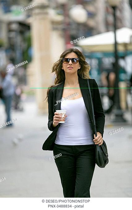 Pretty young woman with sunglasses walking in downtown