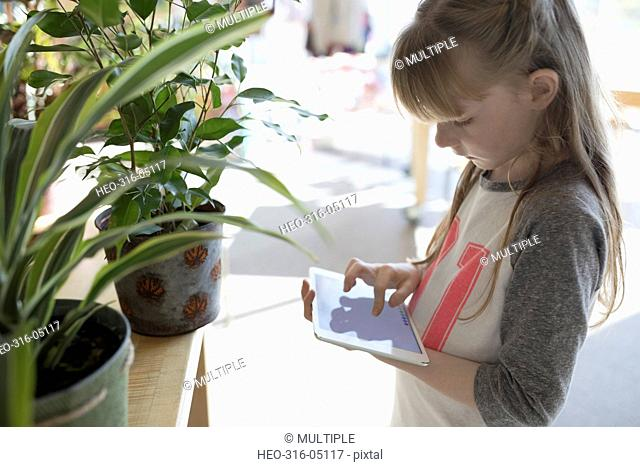 Girl using digital tablet at plant display in science center
