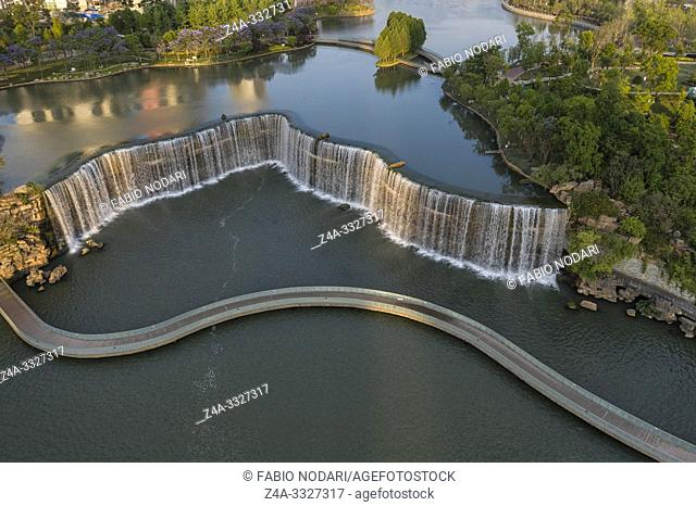 Aerial view of the Kunming Waterfall Park at sunset, one of the largest manamde waterfalls in the world