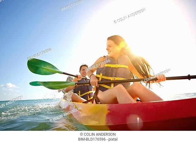 Friends rowing canoe in ocean