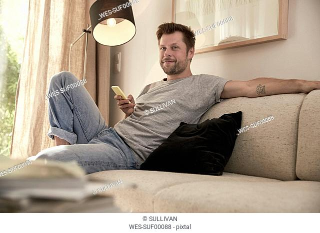 Relaxed man at home sitting on couch with cell phone