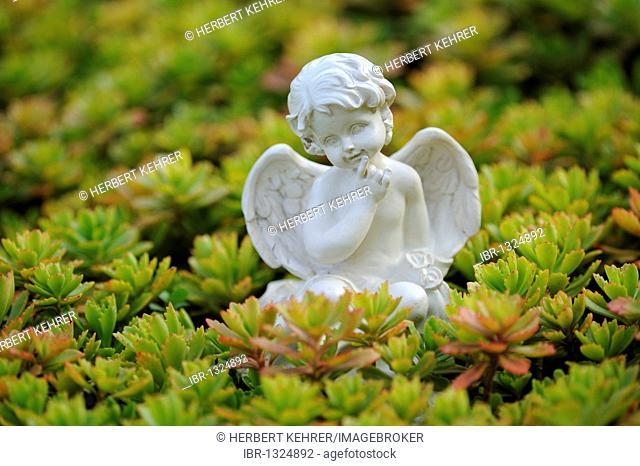 Angel figure as a garden decoration between rockery plants