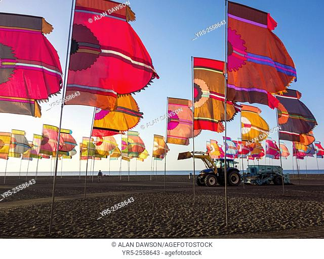 Womad flags on Gran Tarajal beach at sunrise during 2015 Womad music festival as tractor cleans beach. Gran Tarajal, Fuerteventura, Canary Islands, Spain