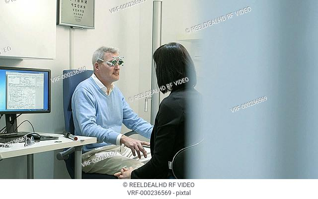 Male patient is instructed to read the Optometrist Test Chart by Female Optician with Oculus Trial Frame. Female Optician exchanges the lenses as he does so