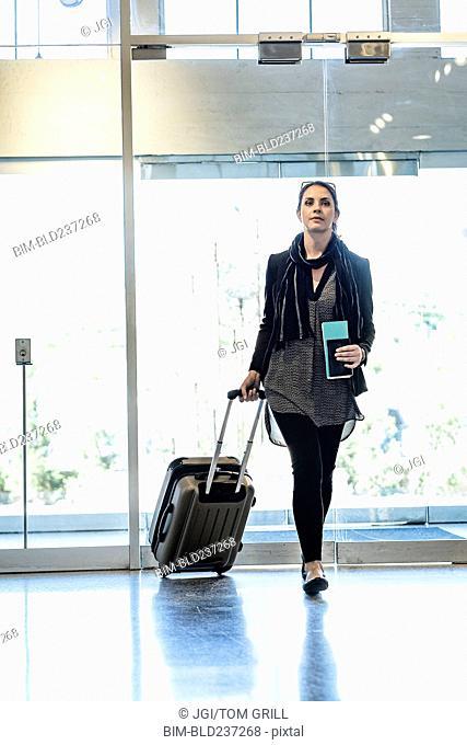 Hispanic woman holding passport pulling suitcase in airport