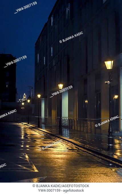Row of street lights along the wet empty road at night, South Kensington, SW7, London, UK