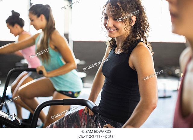 Smiling young woman riding elliptical bike in exercise class
