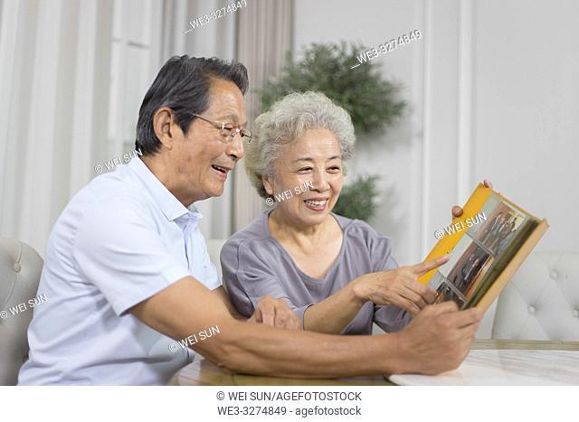 Elderly couple looking at photo album