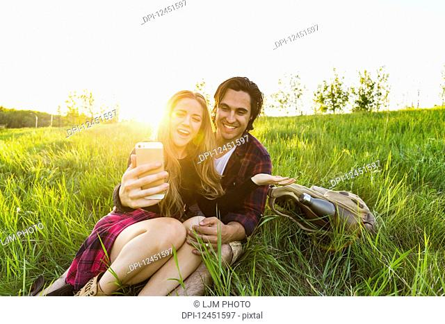 Young couple in a park posing for a self-portrait with their cell phone; Edmonton, Alberta, Canada