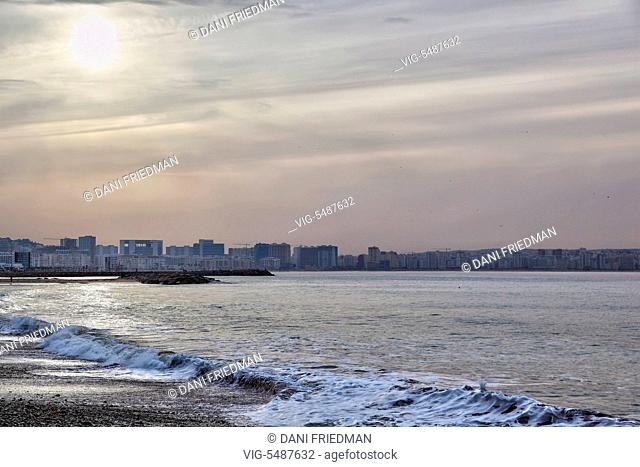 The sun struggles to break through thick cloud cover over the Mediterranean Sea in Tangier (Tangiers), Morocco, Africa. In the distance is the medina and the...