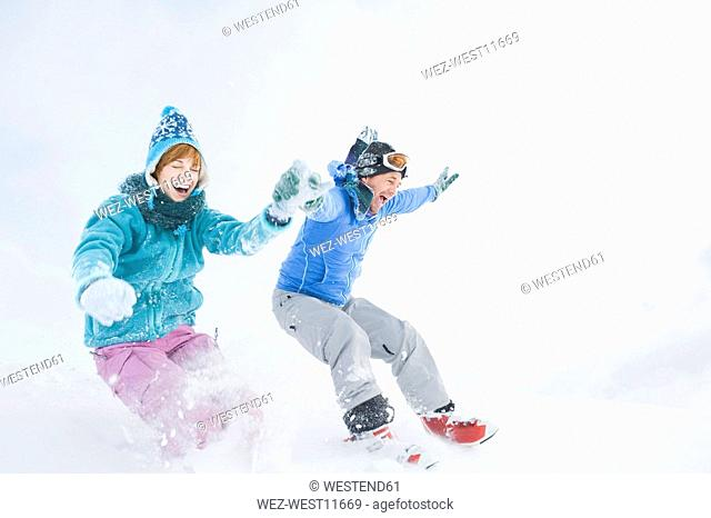Italy, South Tyrol, Seiseralm, Couple holding hands, jumping