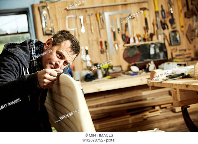 Man standing in a workshop inspecting closely the edge of a wooden surfboard