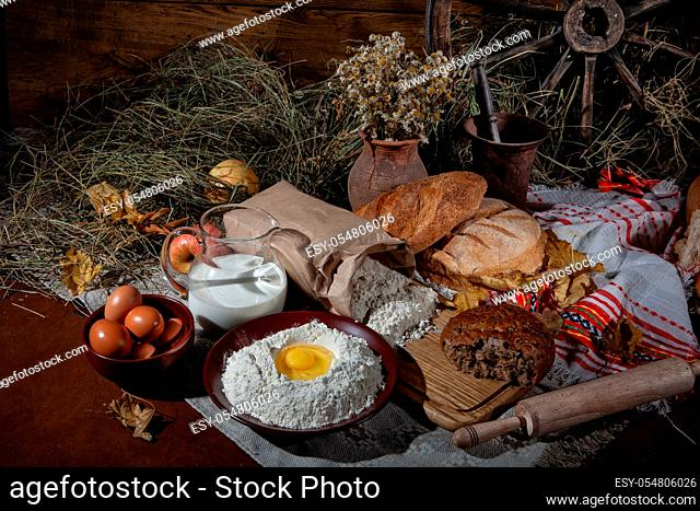 Different kinds of bread and rural accessories on a fabric background