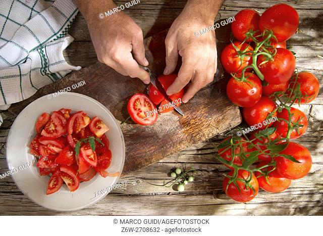Cut and prepare preserves for the winter with smooth round tomato