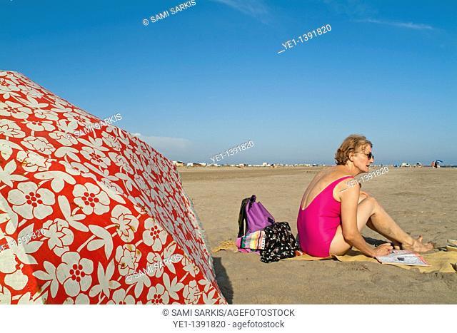 Senior woman reading a magazine at the beach, Camargue, France