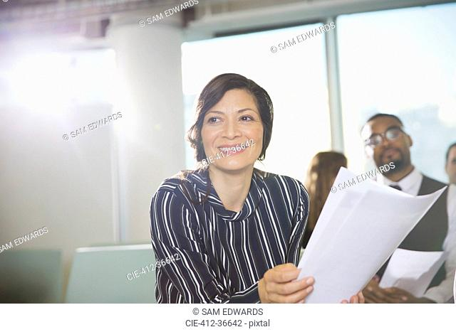 Smiling businesswoman with paperwork in conference room meeting