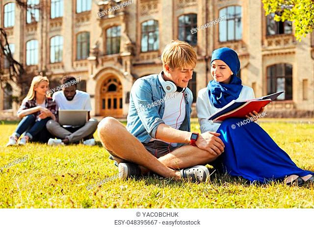 No prejudice. Young intelligent confident guy asking his fellow student for help and meeting her after classes in the backyard near the campus