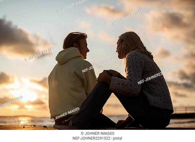 Couple sitting on beach at sunset