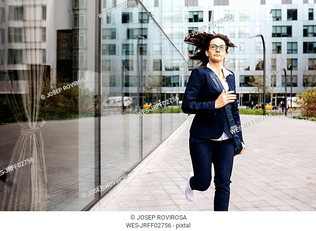 Businesswoman running outside office building in the city