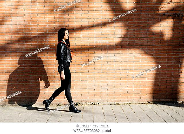 Young woman with a red bag walking in front of a brick wall and a shadow of tree