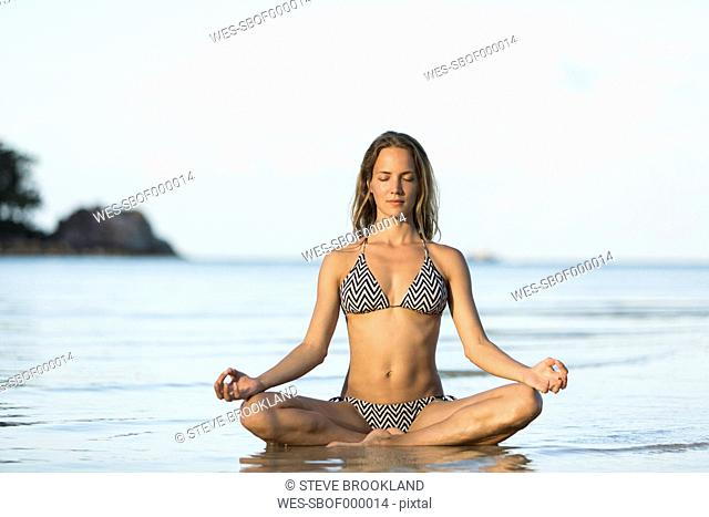 Thailand, woman meditating on beach