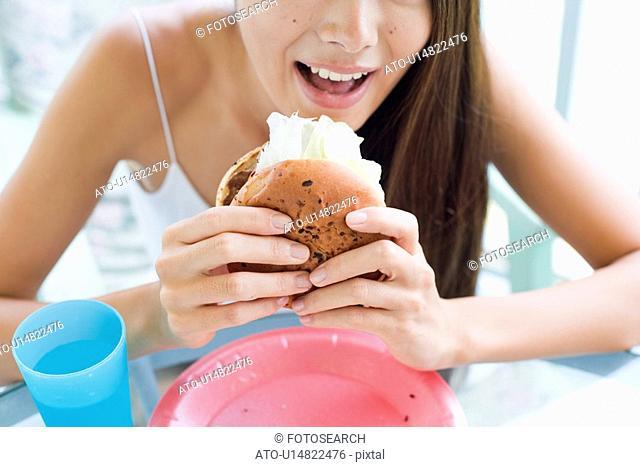 A young woman eating burger