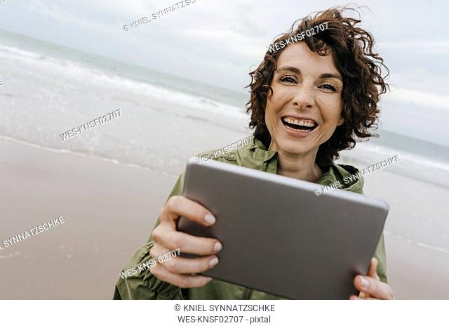 Portrait of happy woman with tablet on the beach