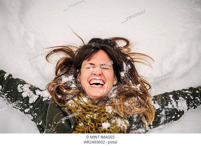 A woman lying on a snow bank with her arms stretched out