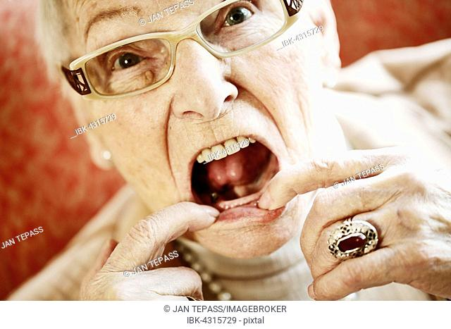 Senior suffering from dementia showing her mouth with missing teeth, North Rhine-Westphalia, Germany