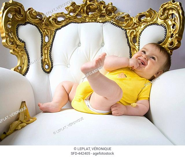 Baby in an ornate armchair with banana skin
