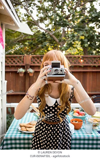Young woman photographing with polaroid camera