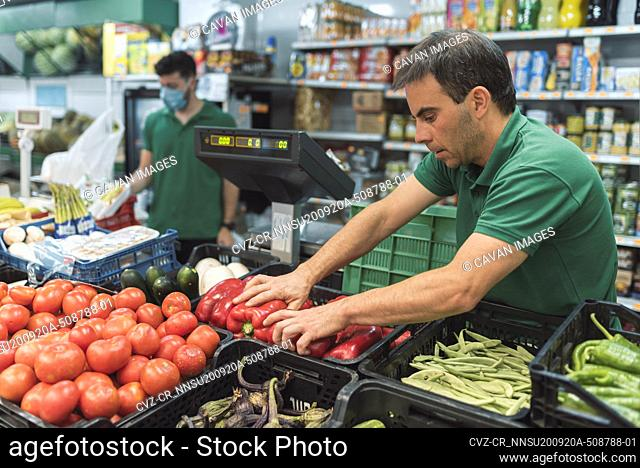 a shopkeeper placing fruit in the greengrocer's