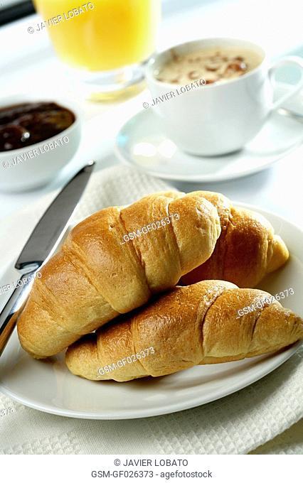 Coffee cup, orange juice, croissants, marmalade