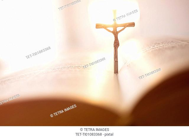 Backlit cross in open Bible
