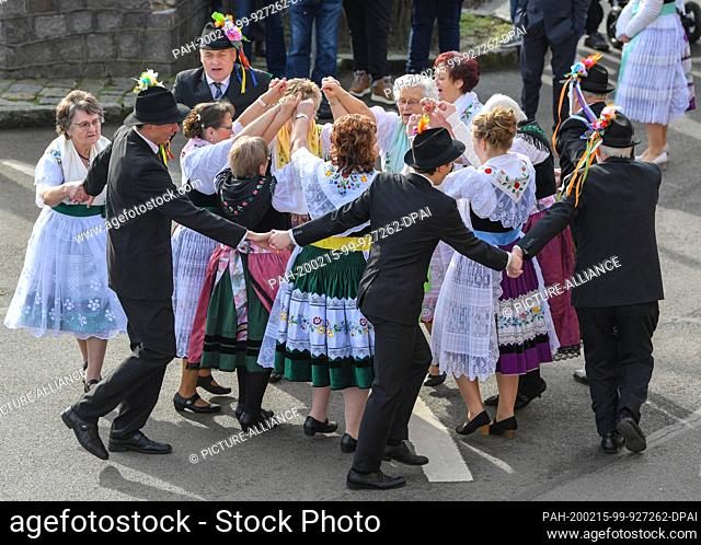 15 February 2020, Brandenburg, Neu Zauche: Couples in original Sorbian-Wendish festive costumes dance on a street during the traditional Zapust, the carnival