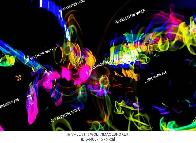 Colorful lights from glow sticks at a dark party using long exposure light effect