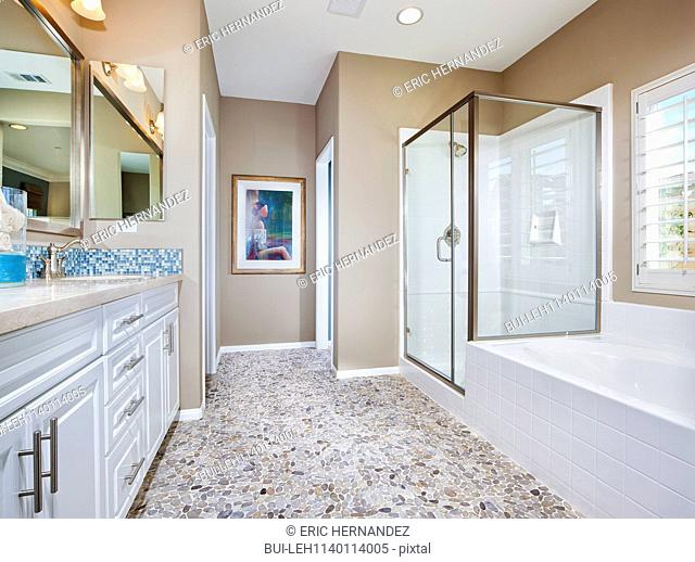 Contemporary bathroom with bath; glass shower and cabinets at home; Menifee; California; USA